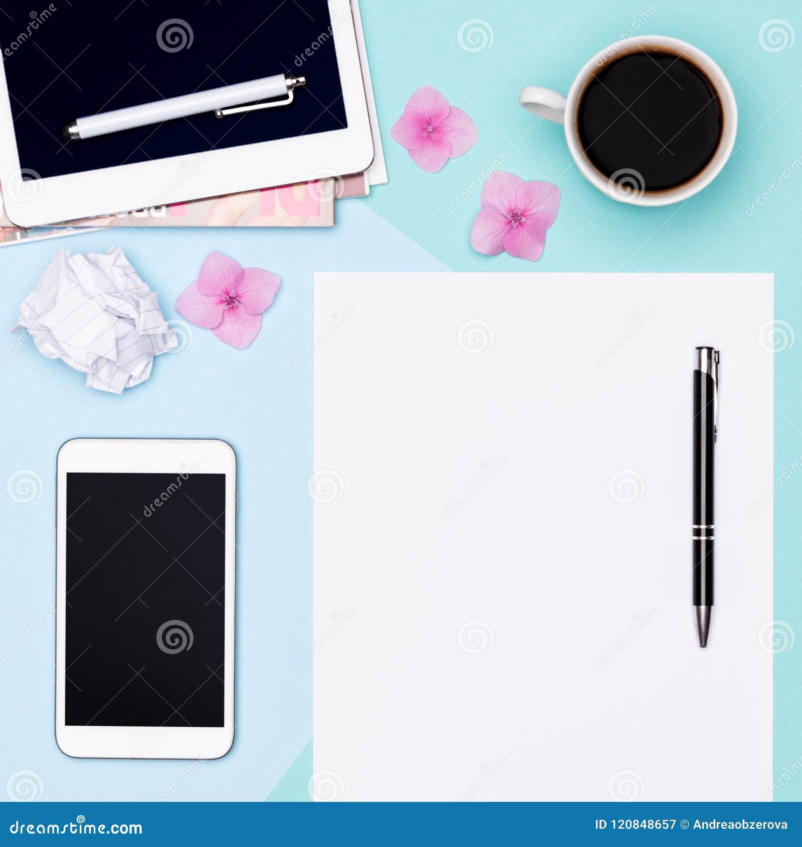 工作区顶视图照片与空白嘲笑的片剂和智能手机、咖啡杯、笔记薄和妇女时装杂志