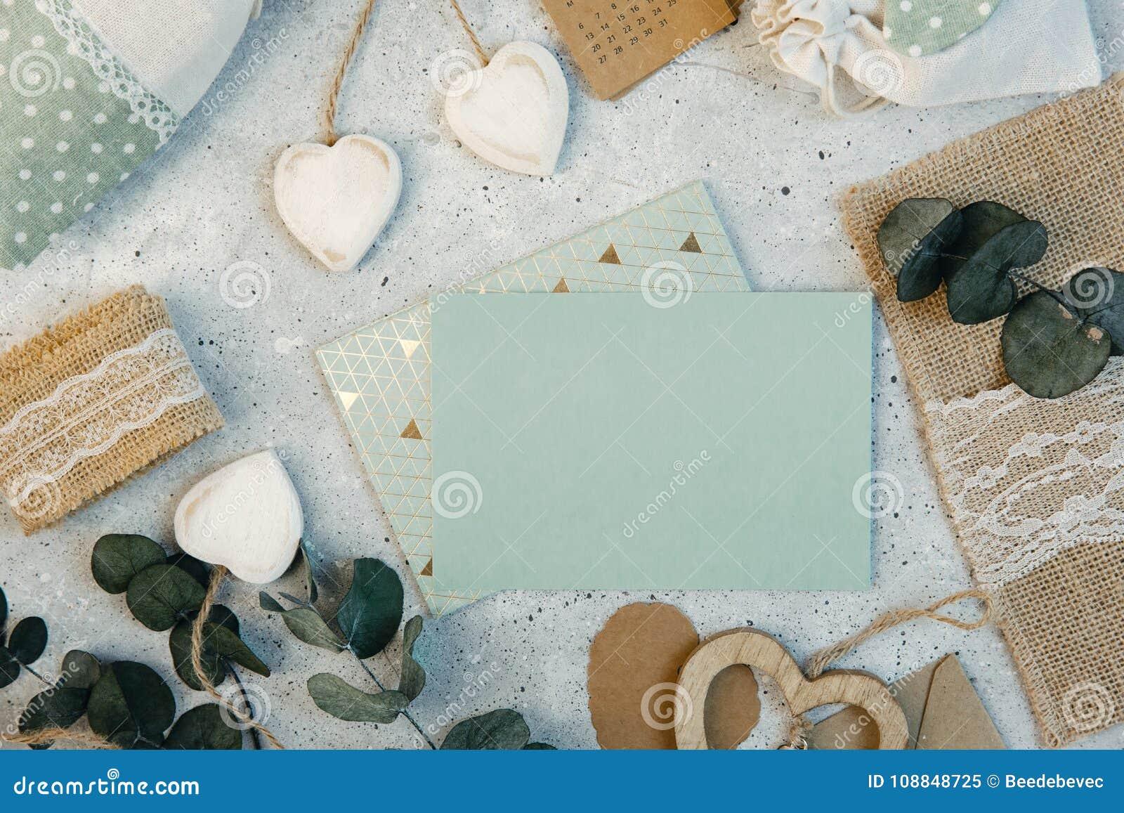 工作区 婚礼邀请卡片、工艺信封、桃红色和英国兰开斯特家族族徽和绿色叶子在白色背景