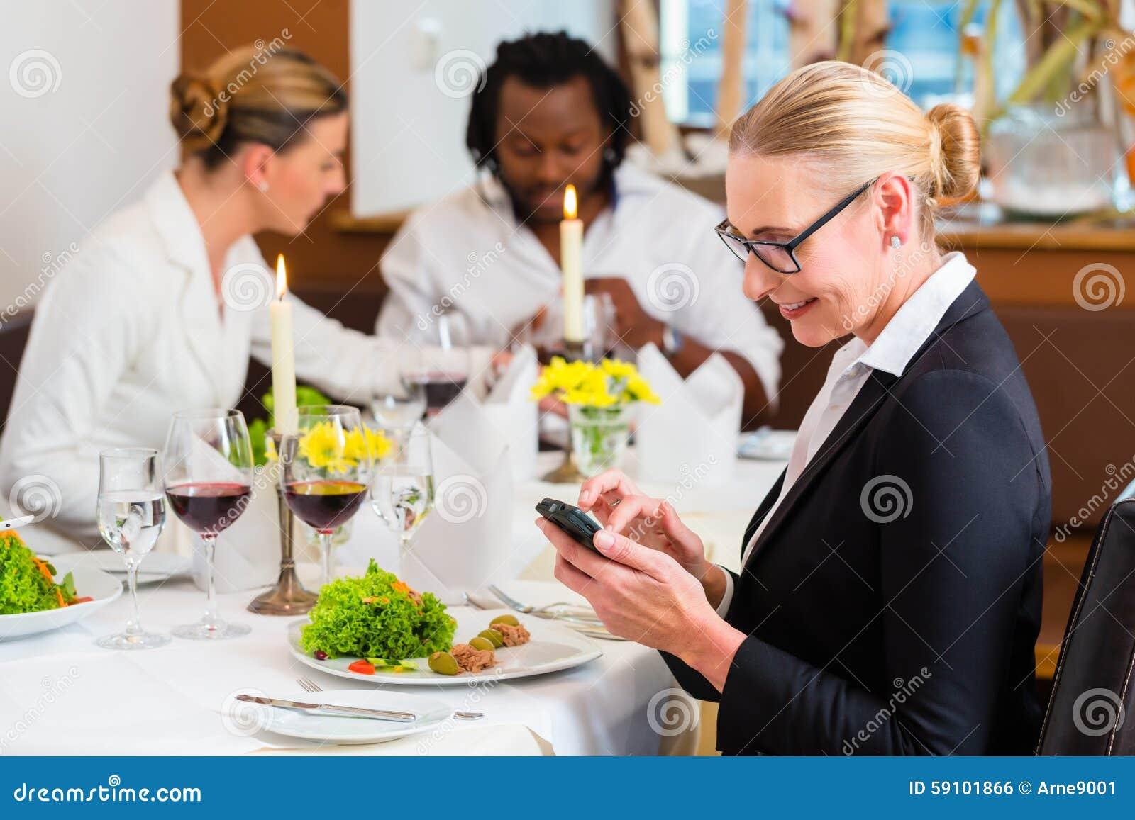 工作午餐的妇女检查在电话的邮件