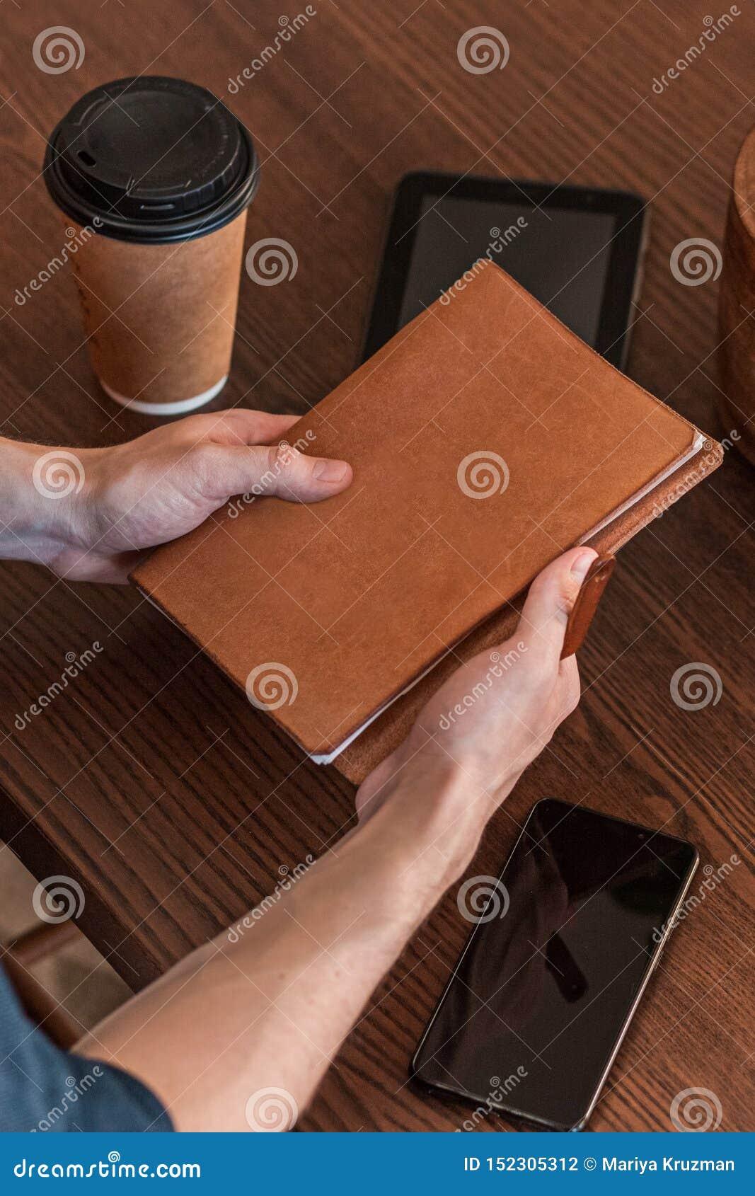 工作在一张书桌在办公室和拿着有copyspace的一个人的特写镜头笔记本