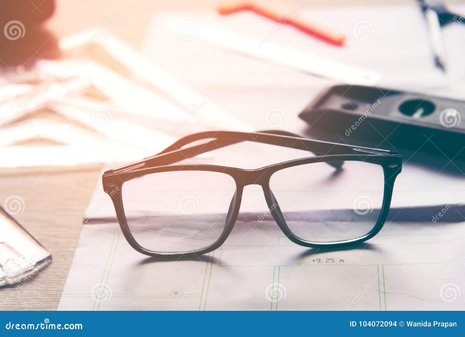 工作在与后面玻璃的图纸的顶视图建筑师 建筑师工作场所