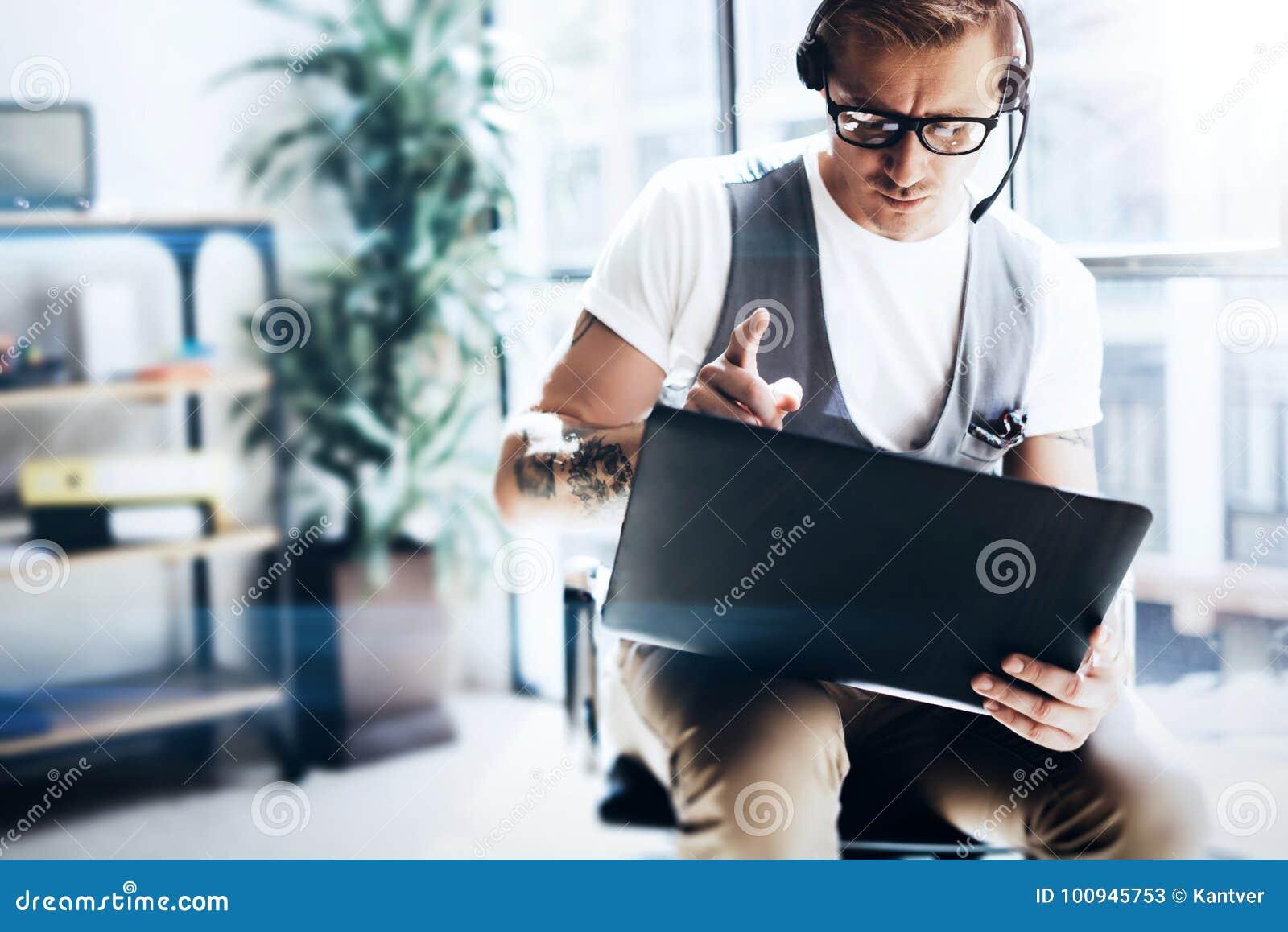 工作在他的举行在手上的数字式片剂的现代办公室的商人 佩带音频耳机的可爱的人和