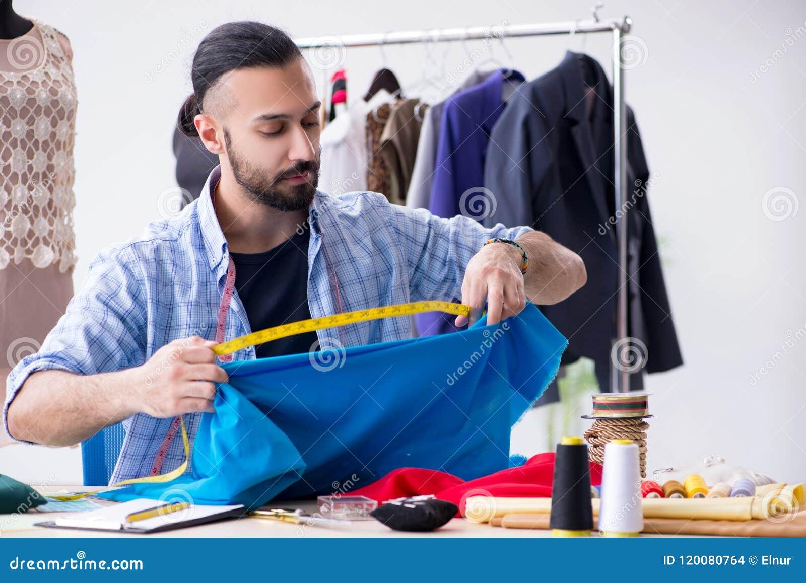 工作在关于新的设计的车间的男性裁缝