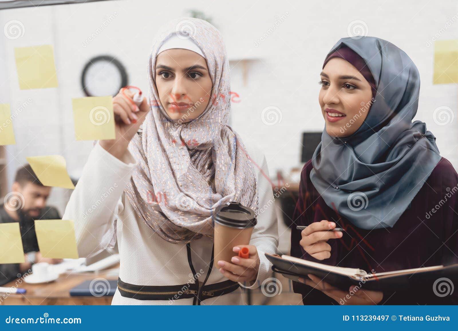 工作在办公室的两名阿拉伯妇女 工友采取关于玻璃委员会的笔记