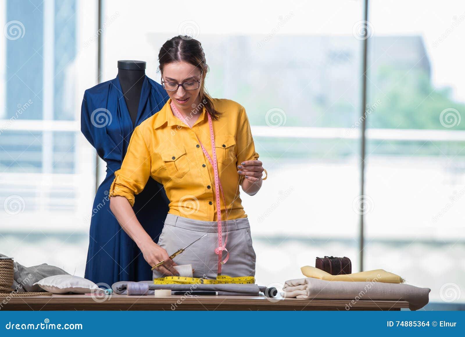 工作在新的衣物的妇女裁缝