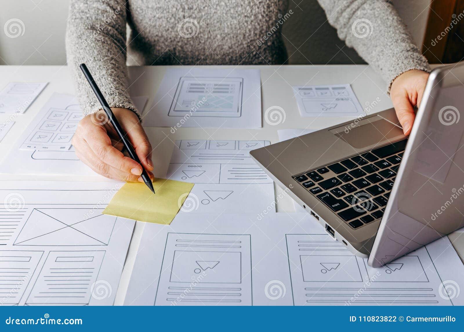工作在膝上型计算机和网站wireframe剪影的网设计师