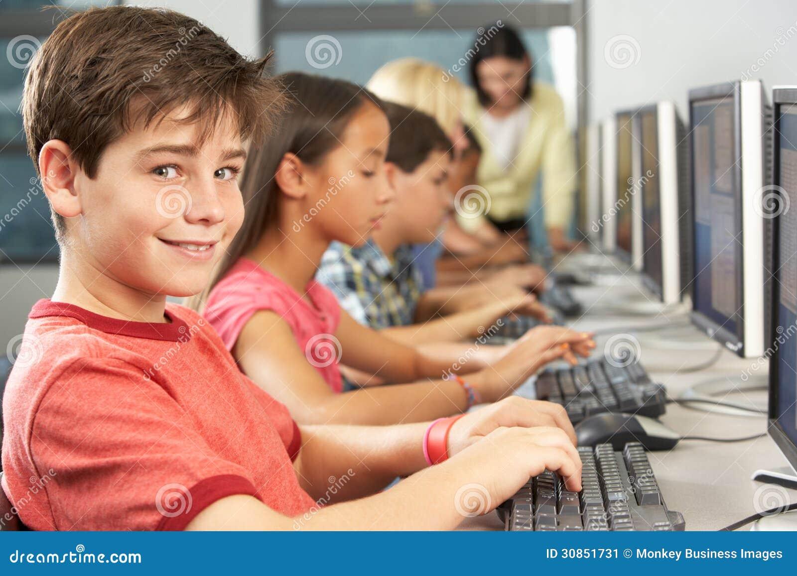 工作在计算机的基本的学生在教室