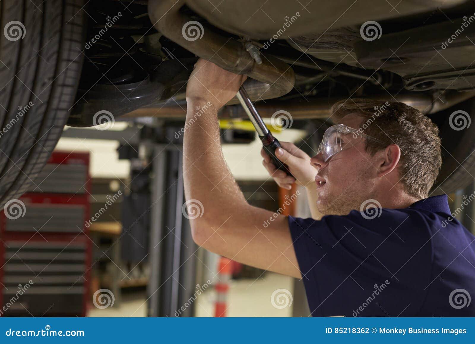 工作在车库的汽车下的汽车机械师