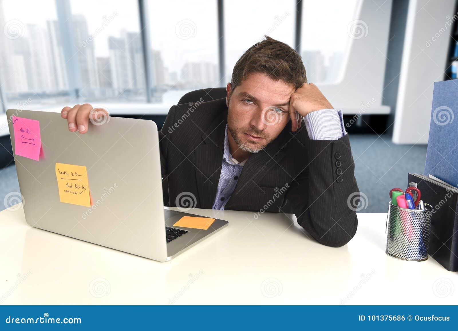 工作在重音的被浪费的商人在办公室看起来的便携式计算机用尽