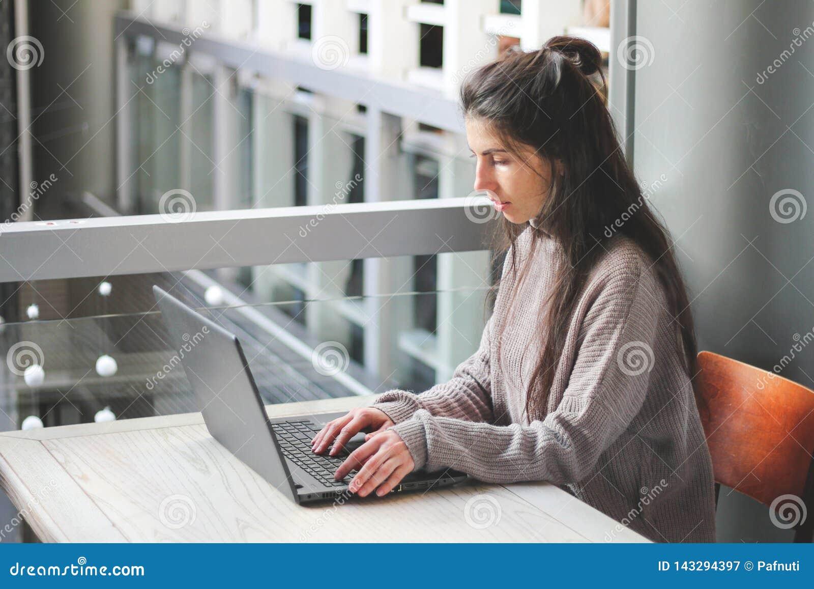 工作在键盘膝上型计算机的咖啡馆手的妇女
