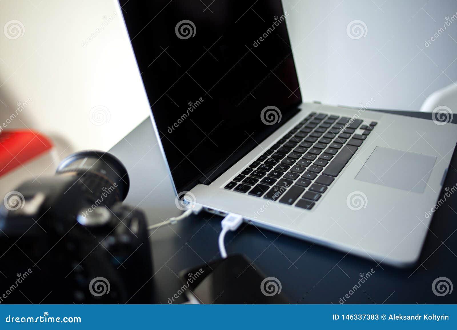 工作场所摄影师和设计师、膝上型计算机有照相机的和智能手机在桌上