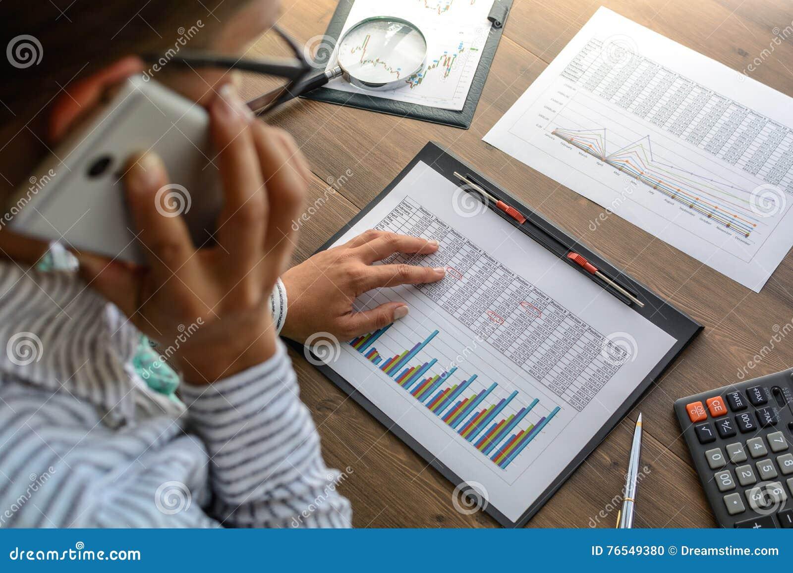 工作场所的女商人在木办公室桌上在计算器, talki分析数据,日程表,定价,做演算