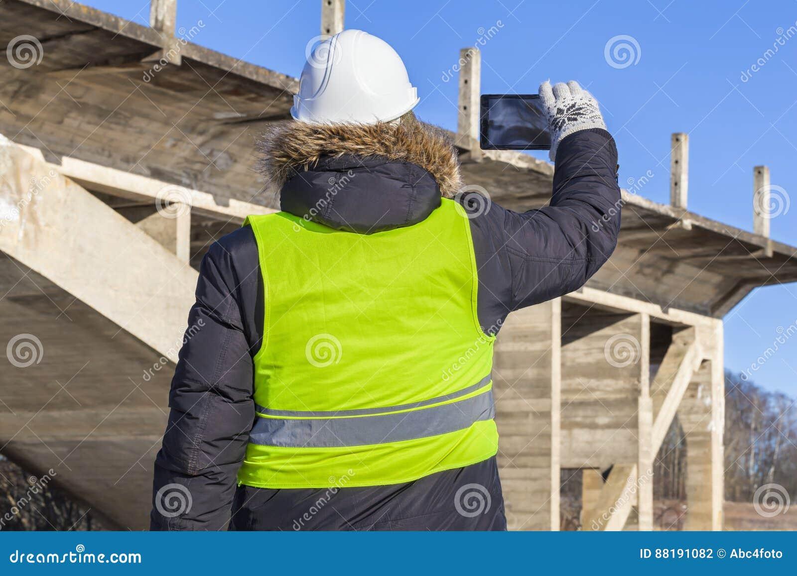 工作者在未完成的桥梁附近拍在片剂的照片