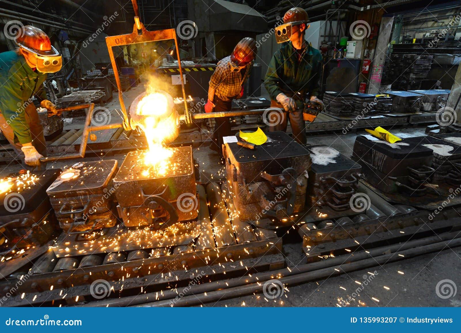 工作者在熔铸金属制件-工作安全的铸造厂和配合