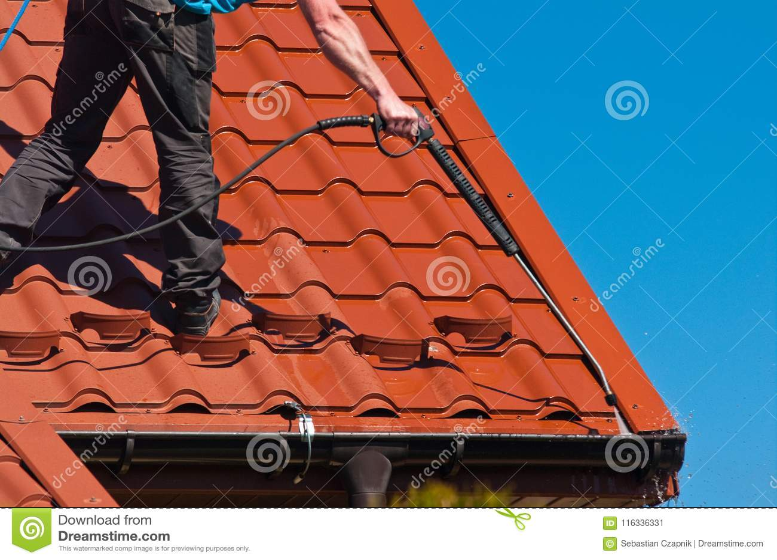 工作者清洁金属屋顶用高压水