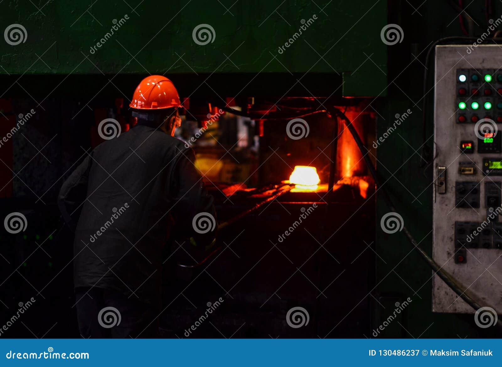 工厂焊接特写镜头的产业工人 在smeltery的热的铁由工作者举行了