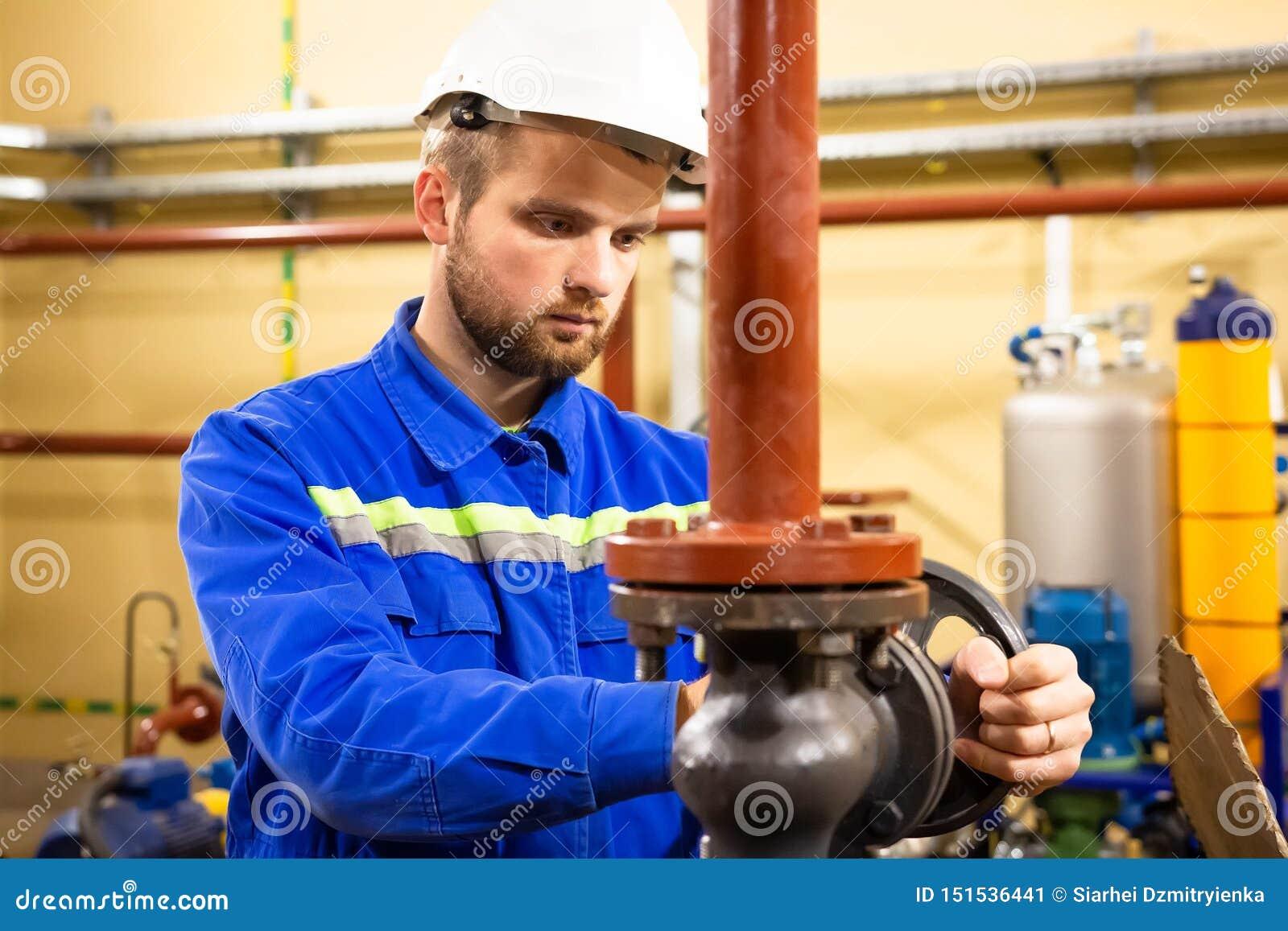 工厂设备的工作者 在锅炉系统的技术员操作员转动的闸式阀 人在盔甲和工作服服务精炼厂
