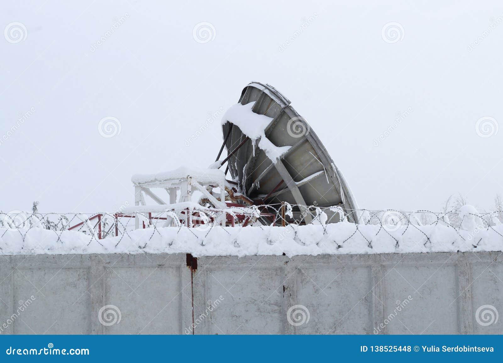 巨大的卫星盘是在有铁丝网的灰色篱芭后
