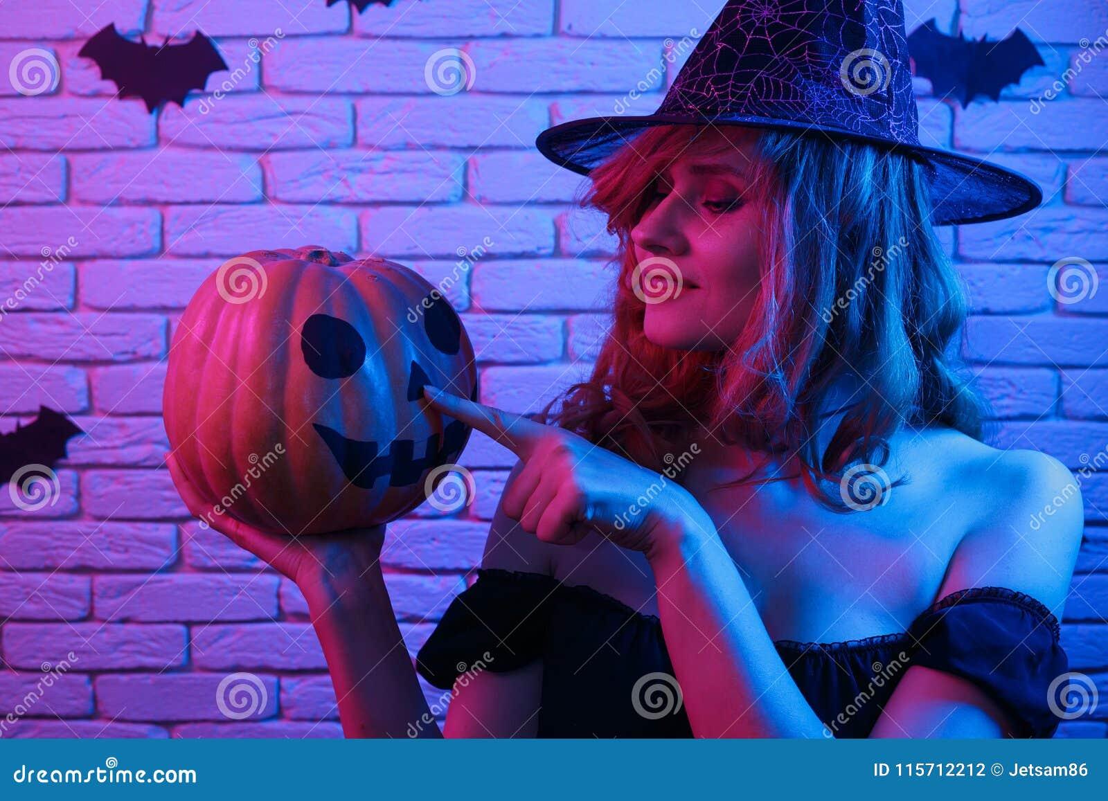 巫婆万圣夜服装的愉快的哥特式少妇用南瓜