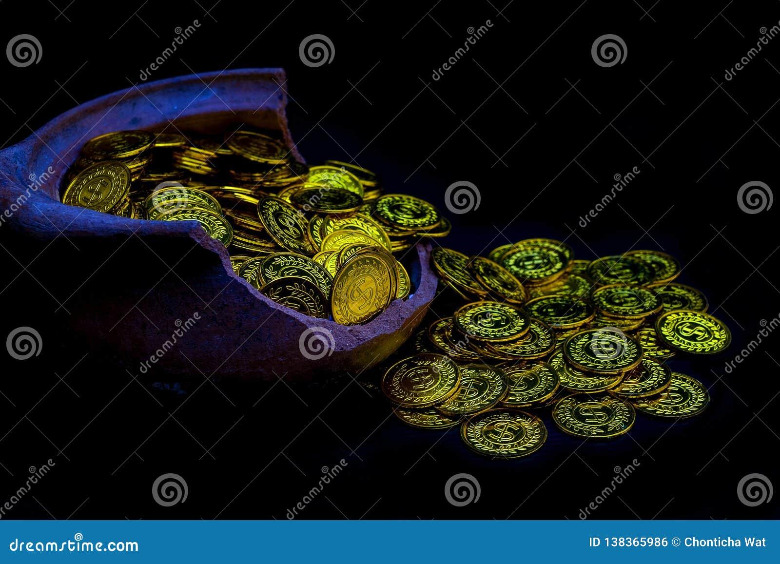 币金在全部的夫人手上在残破的瓶子白色背景,金钱堆中的堆积金黄硬币企划投资的