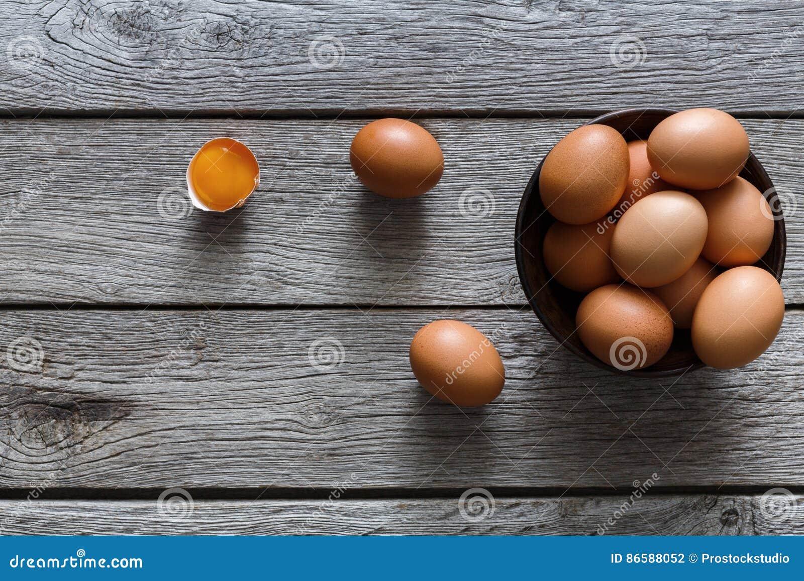 布朗和白色有机鸡蛋在碗在木背景