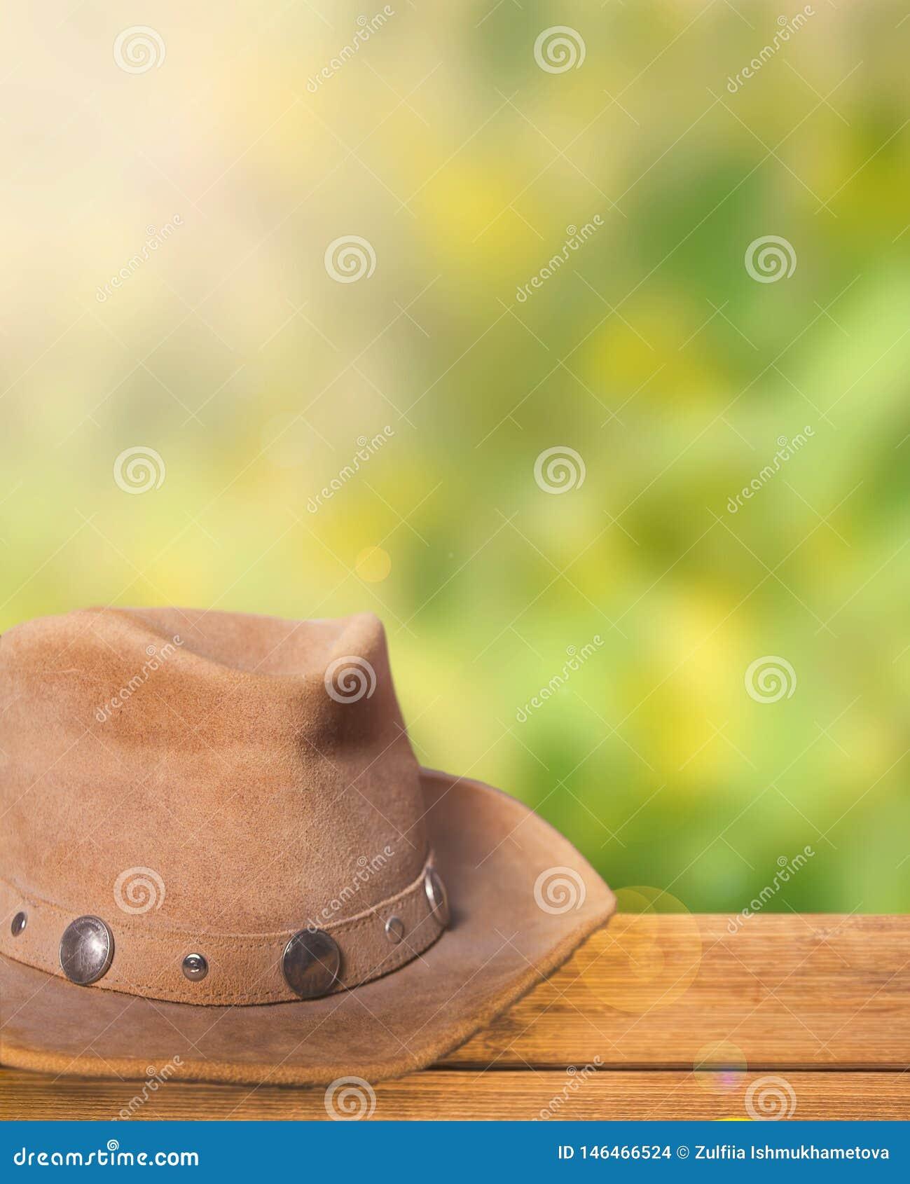 布朗在一张木桌上的牛仔帽与在背景的自然