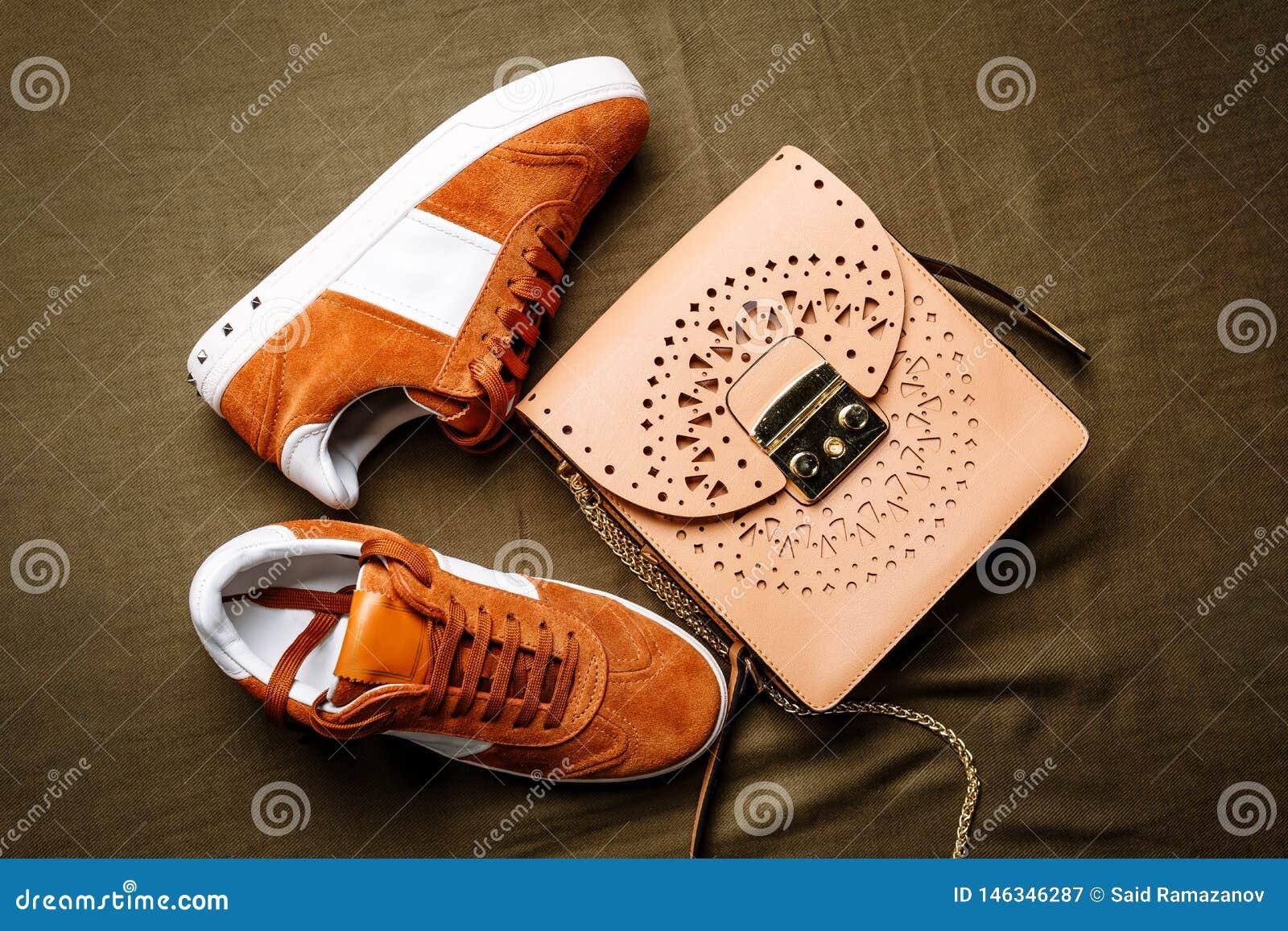 布朗有白色口音的绒面革运动鞋在白色脚底和一个棕色皮包与一把金黄锁在绿色被编织的背景