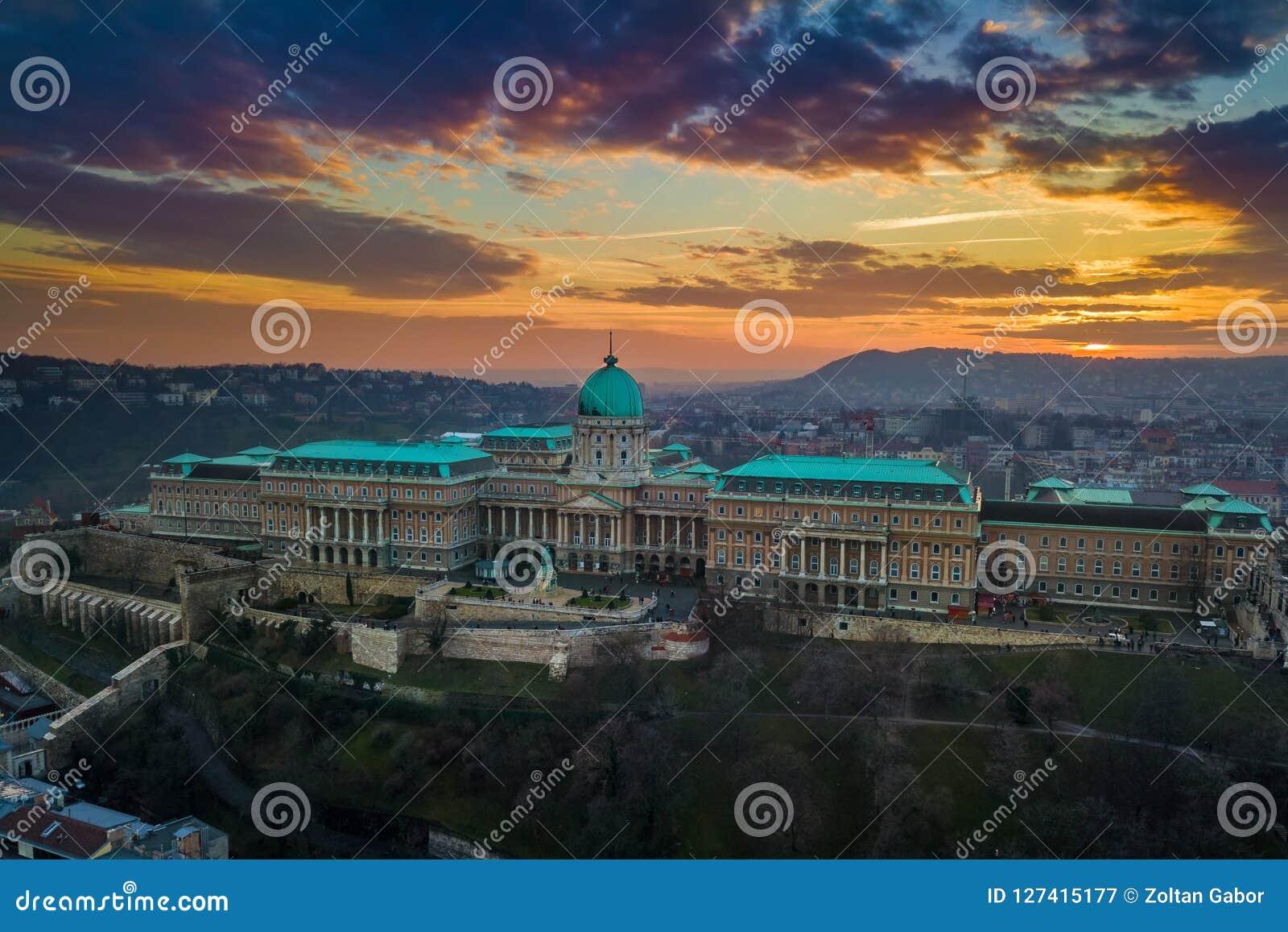 布达佩斯,匈牙利-著名布达城堡王宫的空中全景日落的与惊人的五颜六色的天空