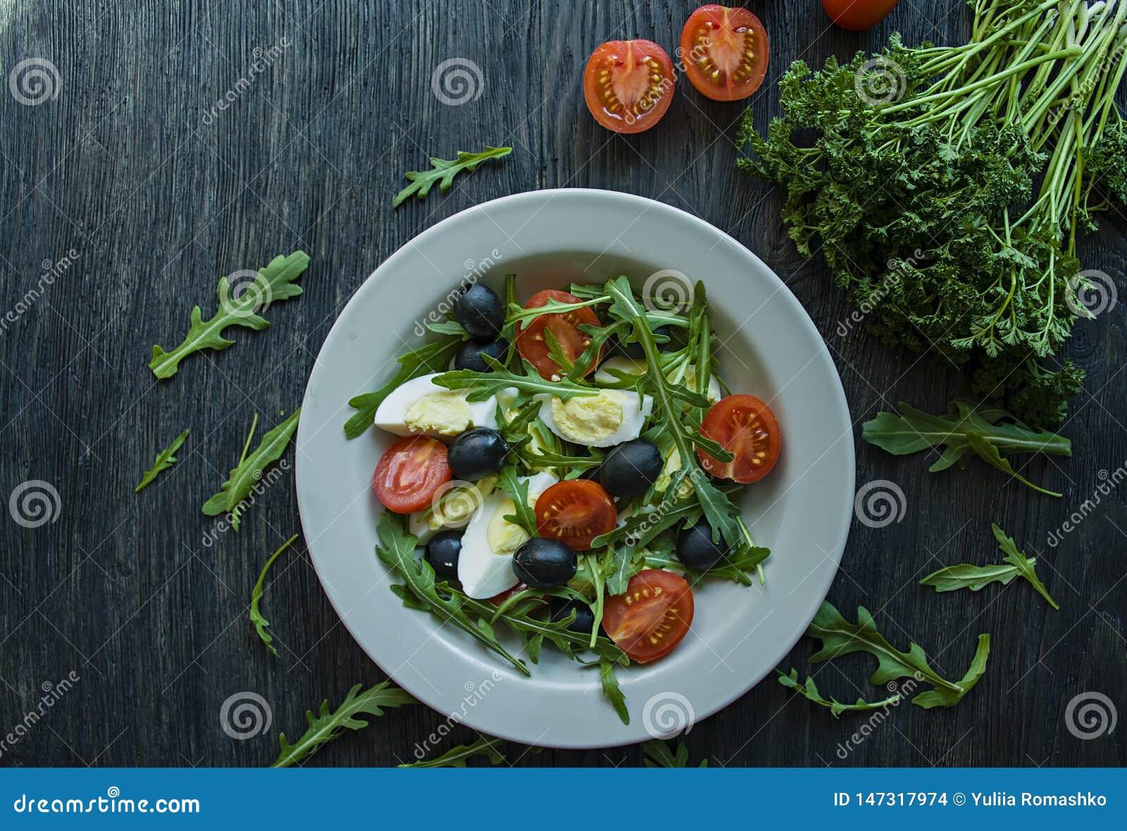 希腊沙拉用新鲜的蕃茄,芝麻菜,鸡蛋,与橄榄油的橄榄在黑暗的木背景 r 素食者盘