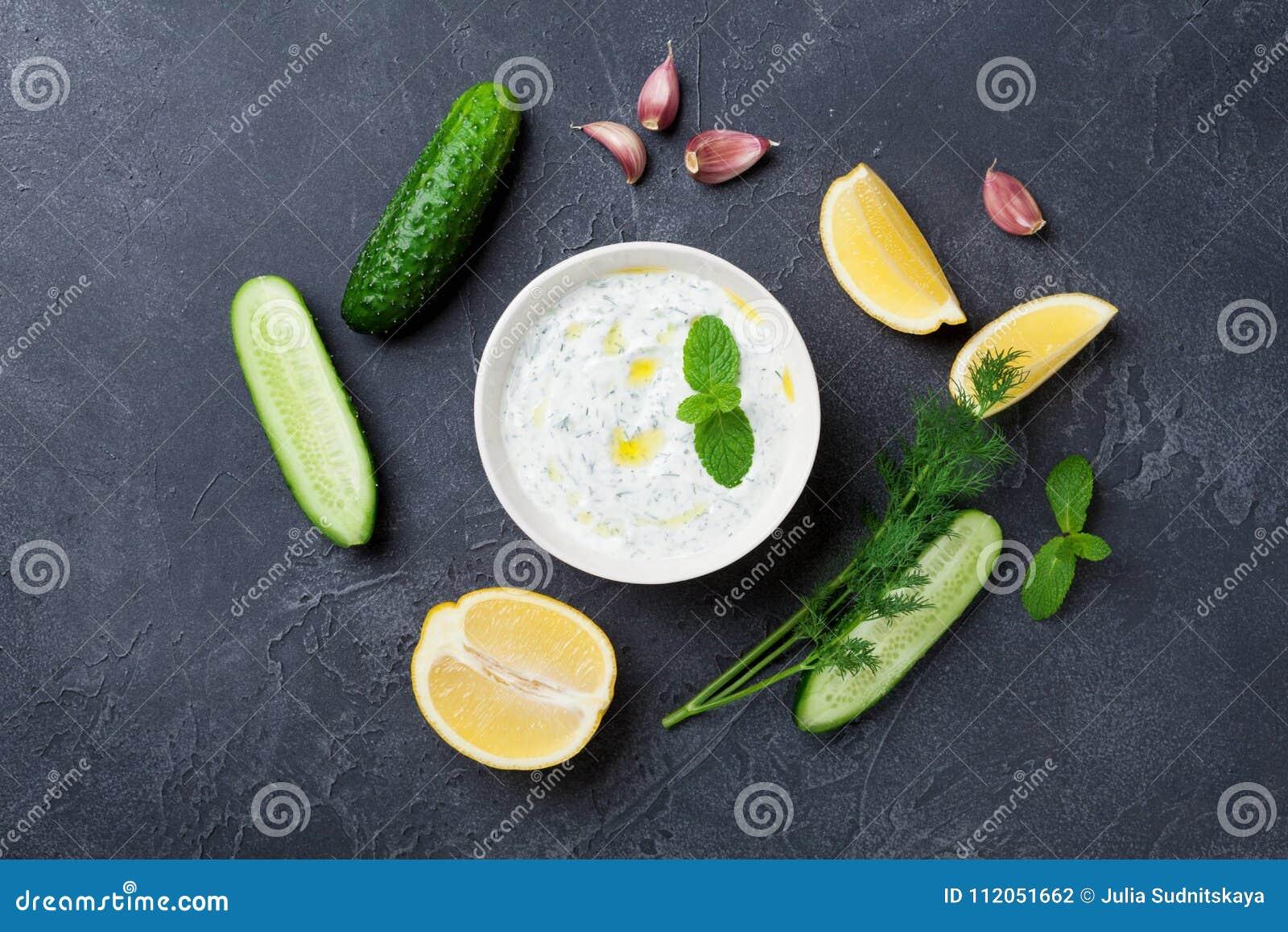 希腊酸奶调味汁tzatziki用黄瓜、莳萝、柠檬、薄菏和大蒜在石台式视图