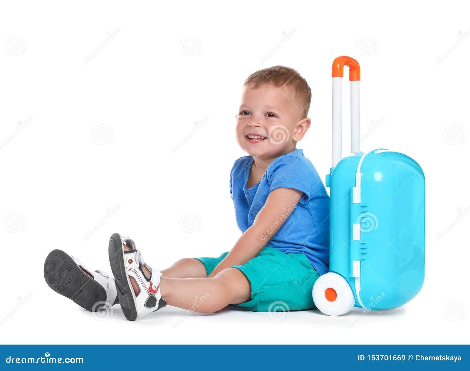 带着蓝色手提箱的逗人喜爱的小男孩在白色