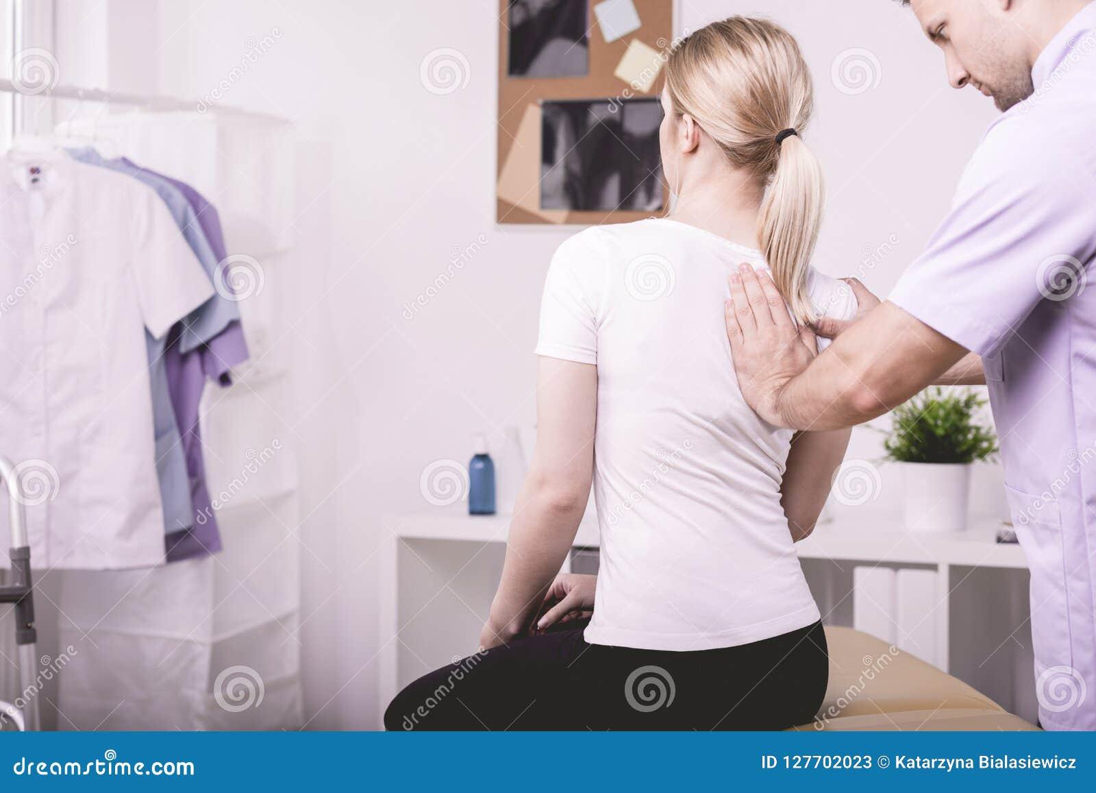 帮助有一块弯曲的脊椎的生理治疗师患者