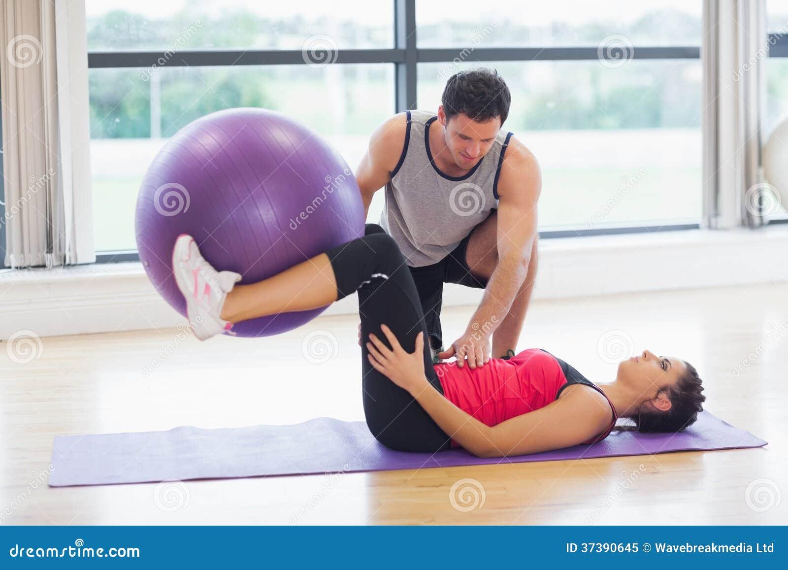帮助有健身球的教练员少妇在健身房