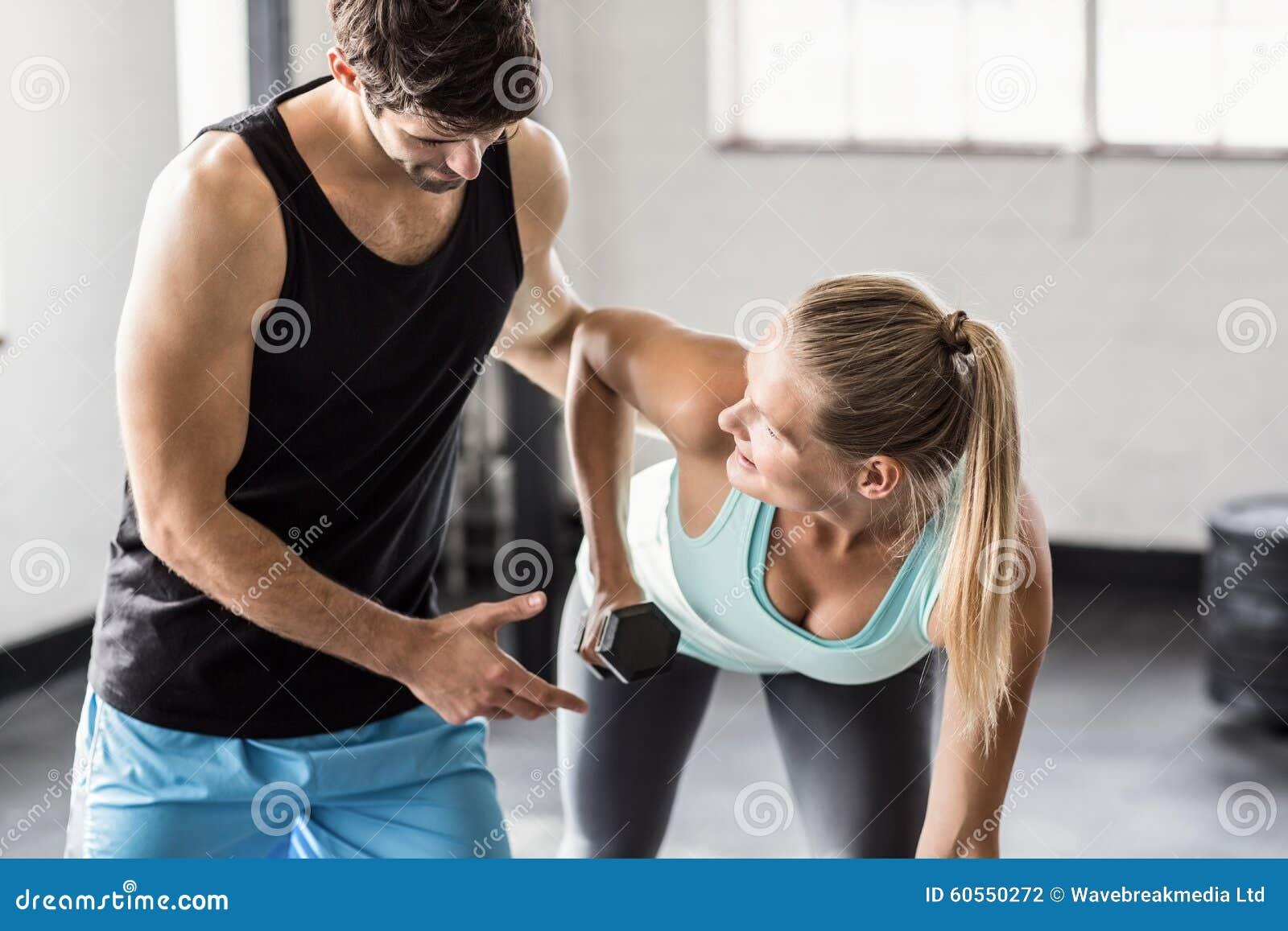 少妇给男人喂_帮助有哑铃的男性教练员少妇在crossfit健身房.