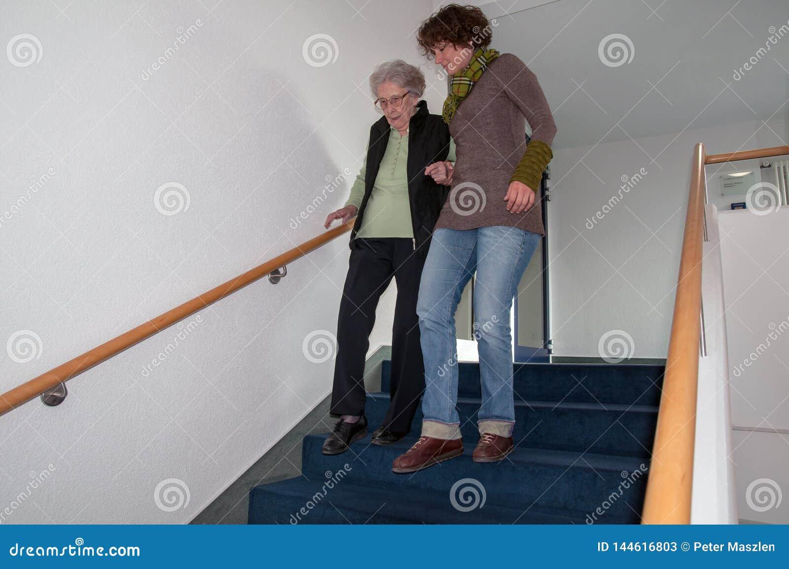 帮助资深妇女的照料者步行沿着向下台阶