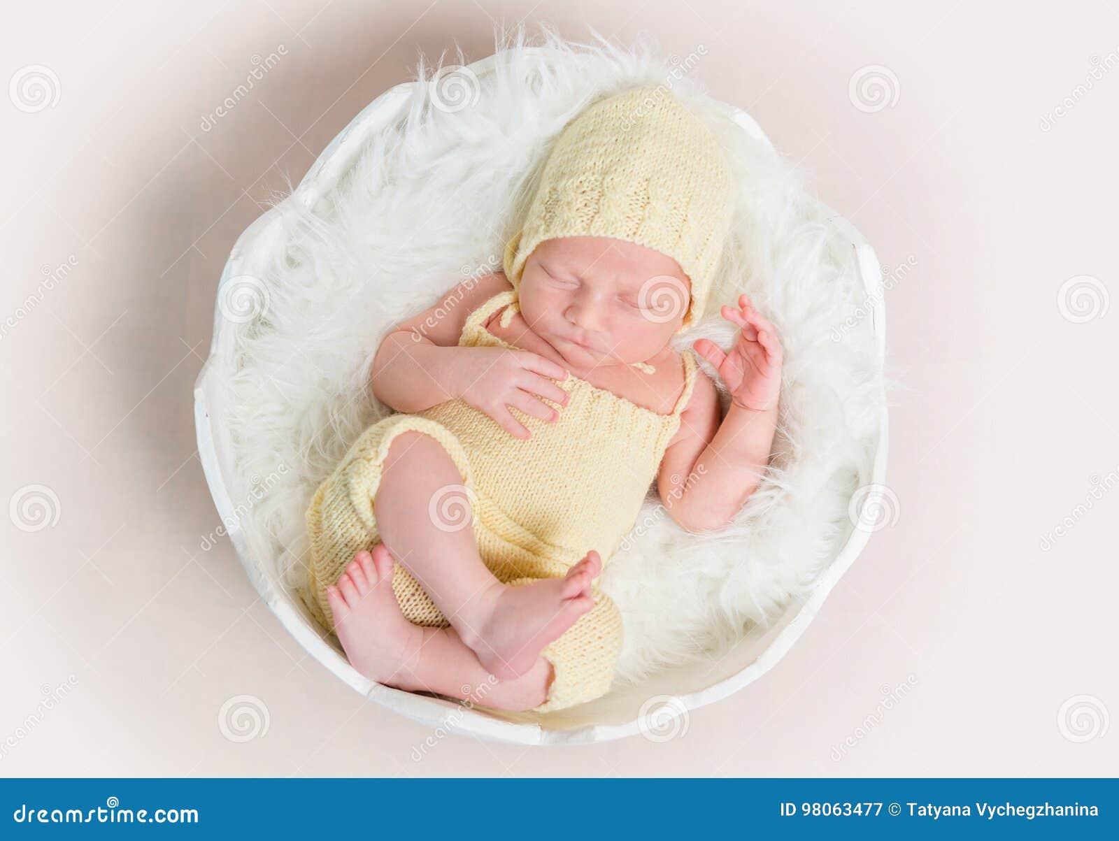 帽子和内裤的甜新出生的婴孩睡觉在壳的