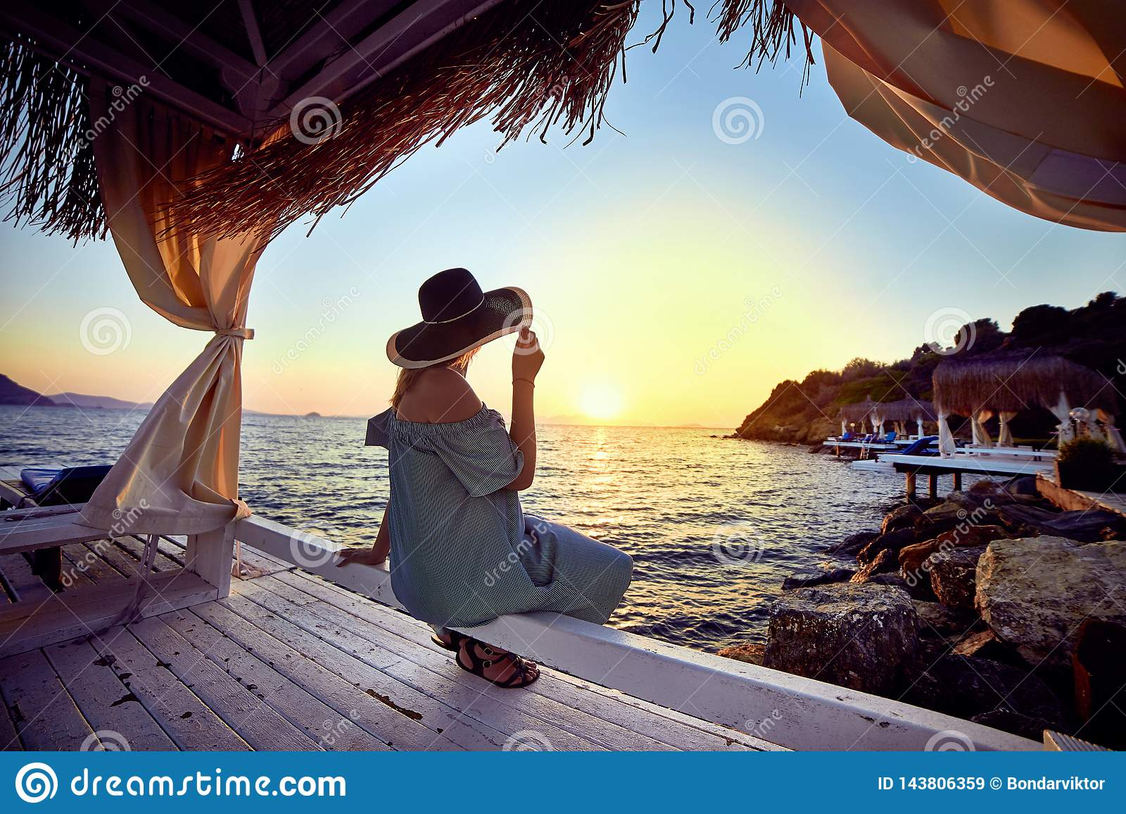 帽子的妇女放松由一种豪华海滩前的旅馆手段的海在日落享受完善的海滩假日假期的