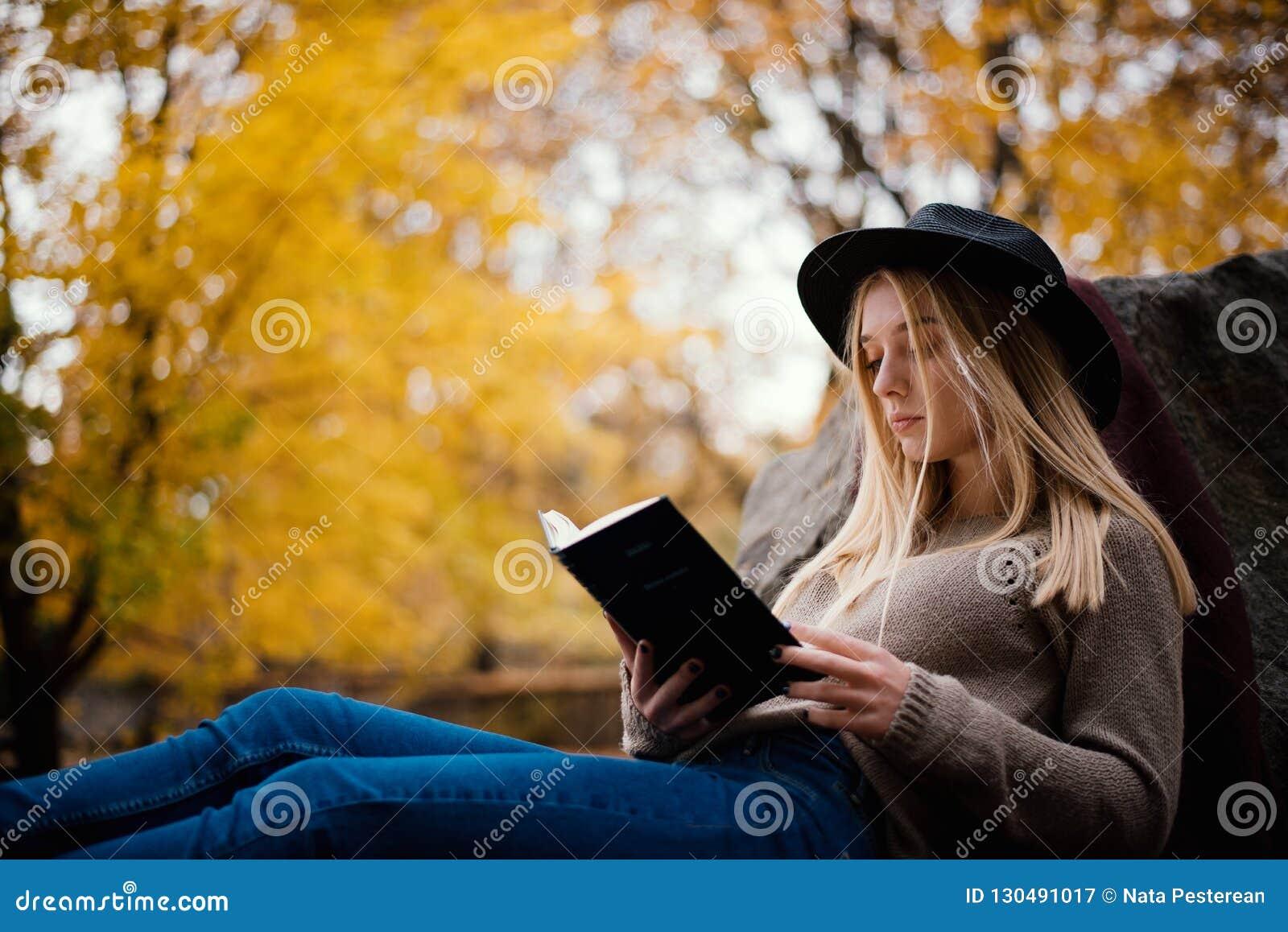 帽子的美丽的年轻金发碧眼的女人坐下落的秋叶在公园,读书
