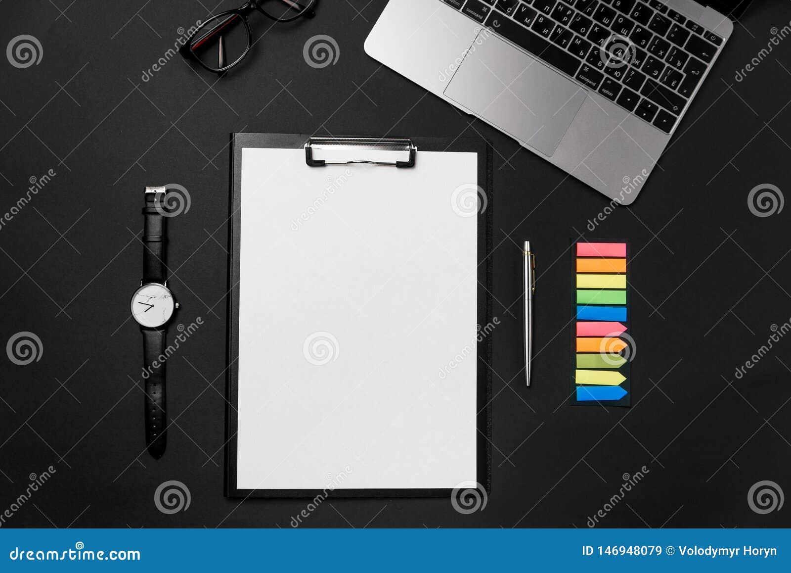 干净的白色纸片与赠送阅本空间、膝上型计算机、手表和笔的在黑backgroun