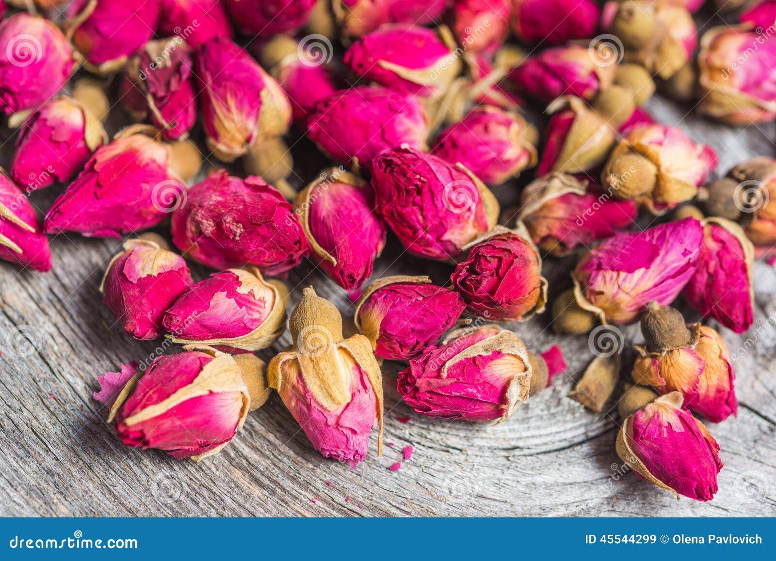 干玫瑰色_干在老木背景的茶玫瑰色芽.