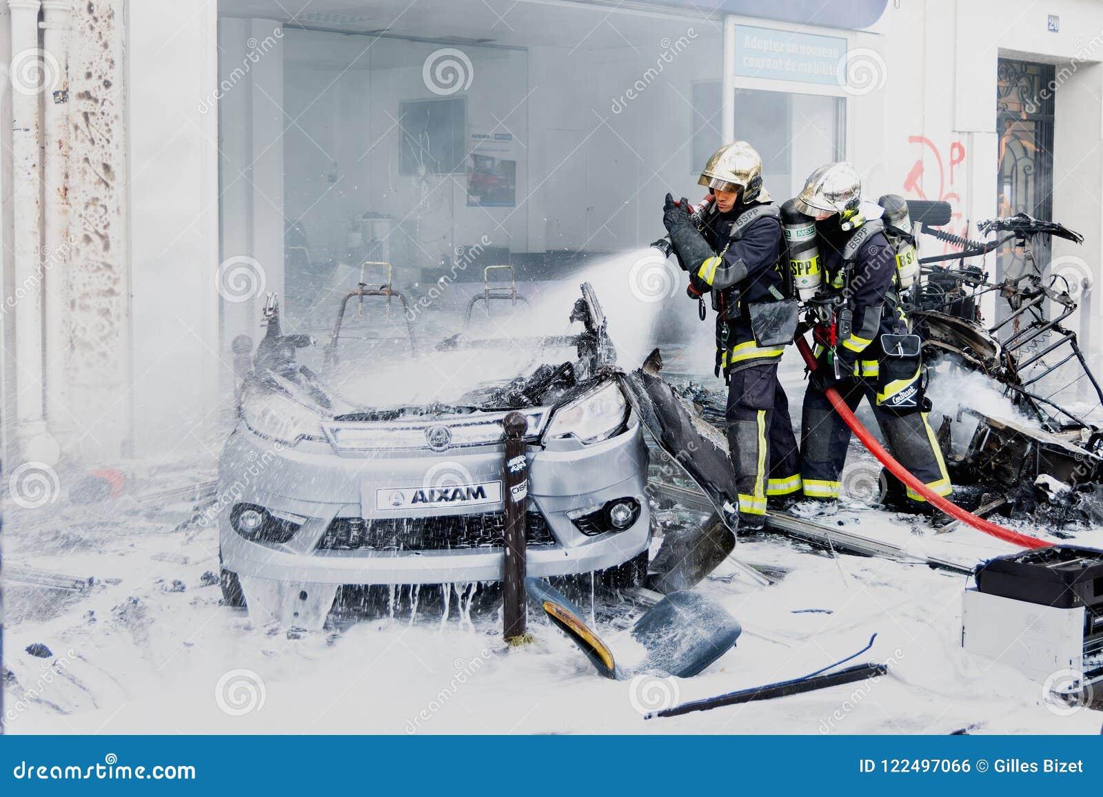 干预的两名消防队员在被烧的汽车