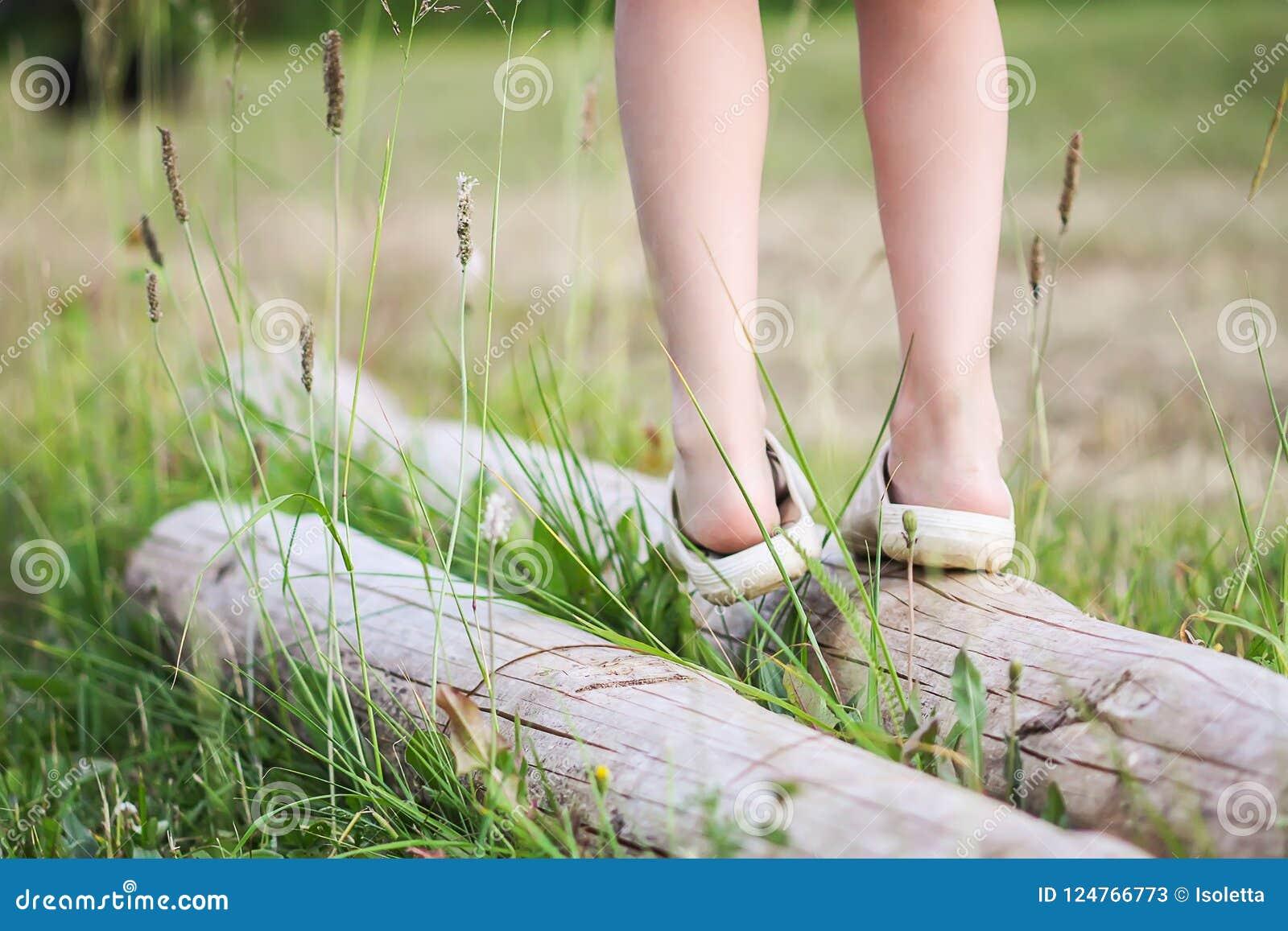 平衡在注册夏天公园的小女孩 Child& x27; s腿和绿草关闭