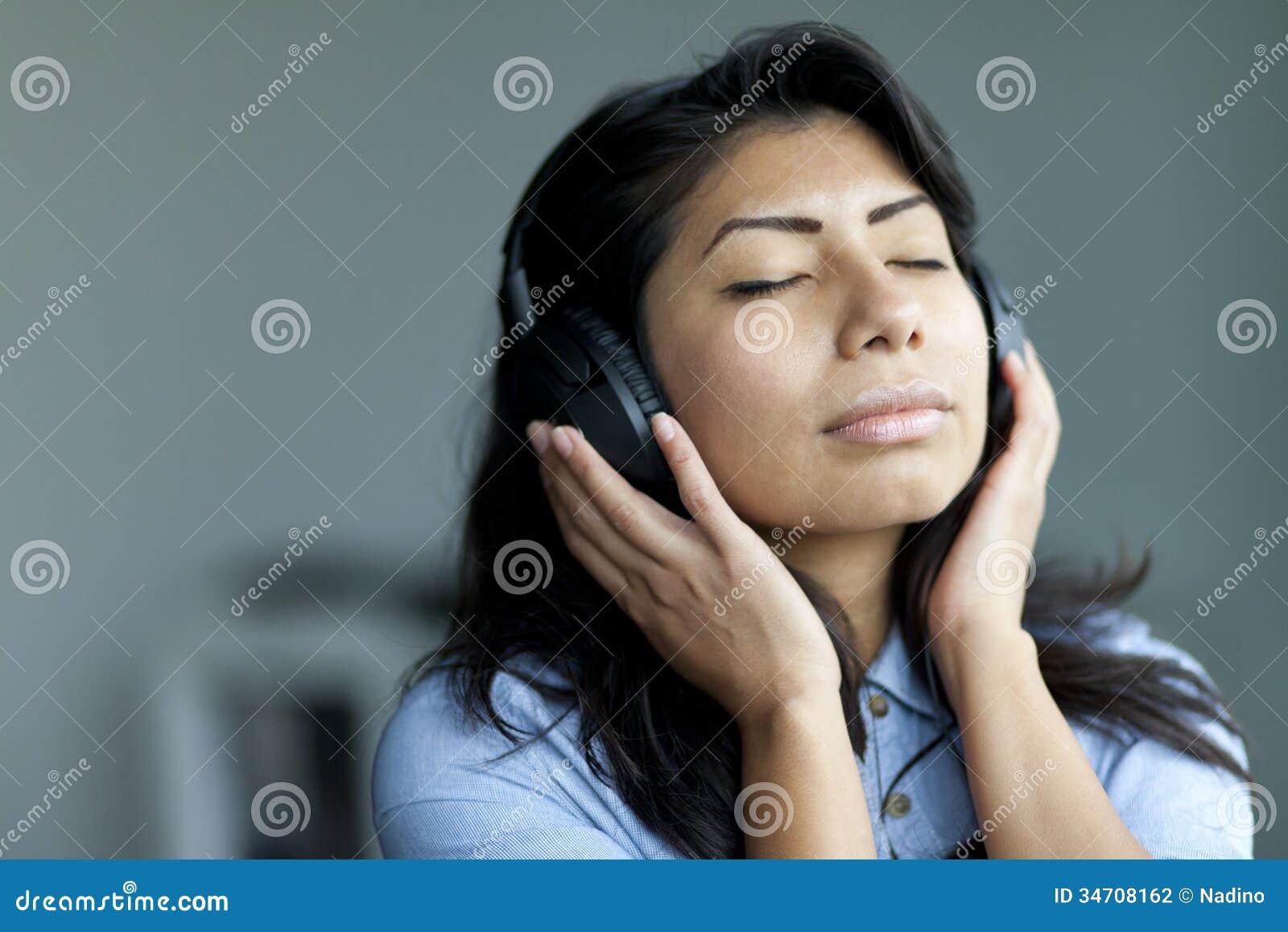 平静的西班牙妇女听的音乐的画象