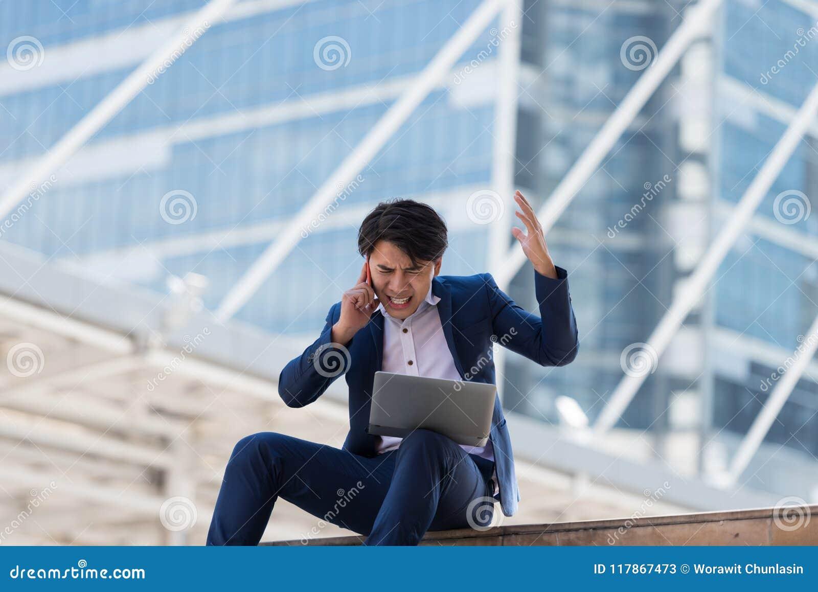 年轻亚洲商人谈话在有严肃的f的手机