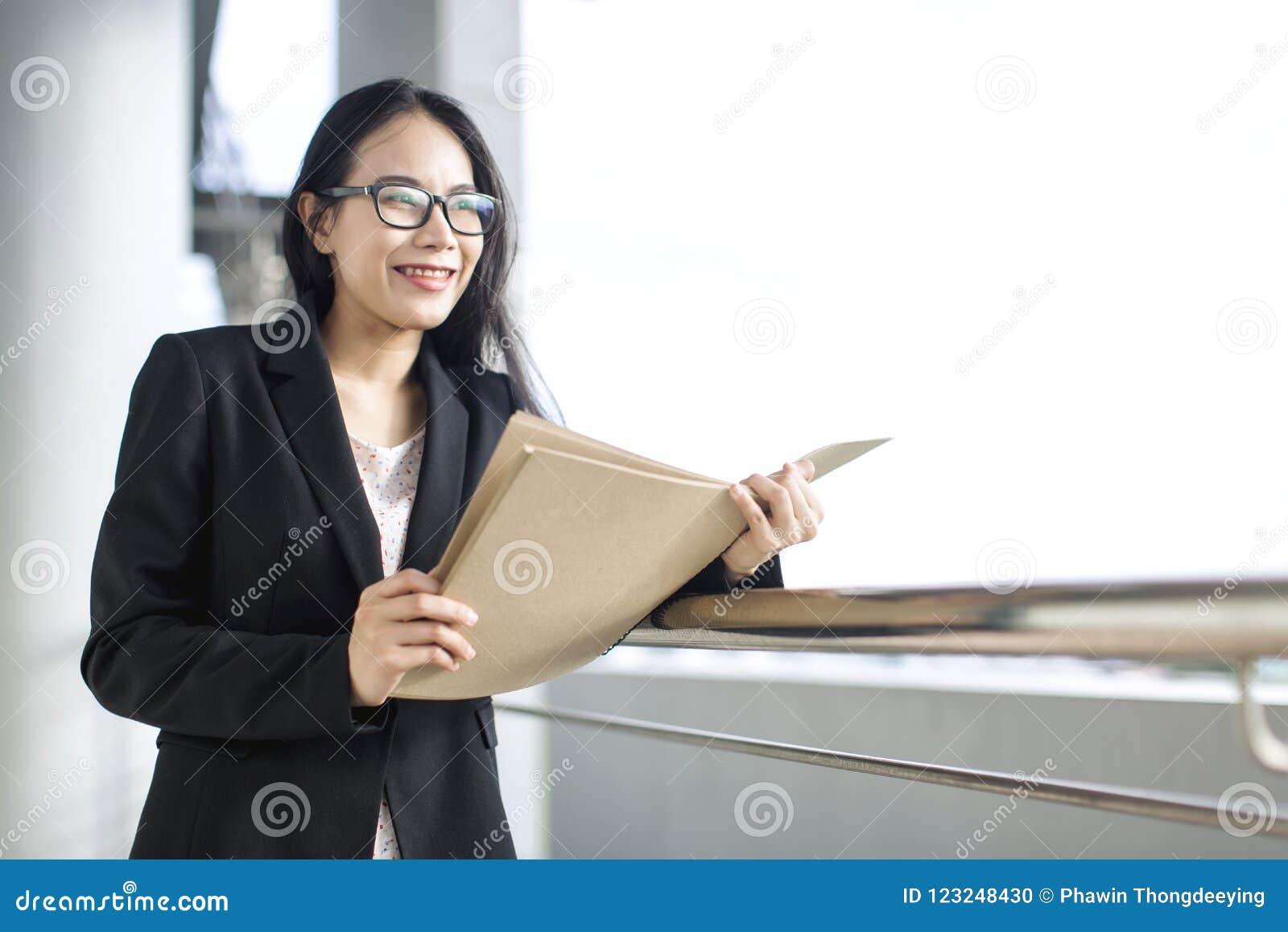 年轻亚洲女商人穿戴衣服待办卷宗文件