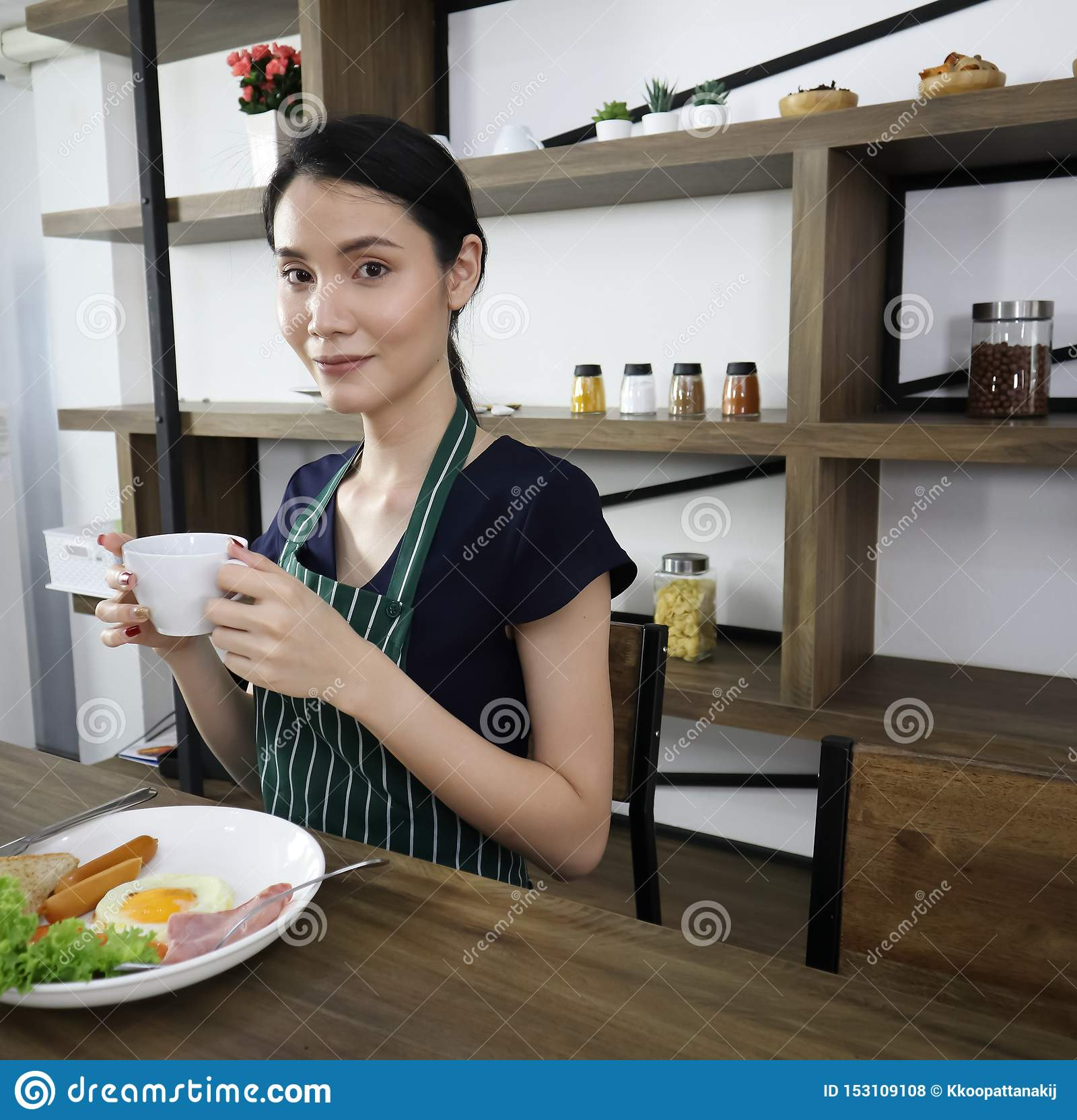 年轻亚洲妇女举行杯子无奶咖啡