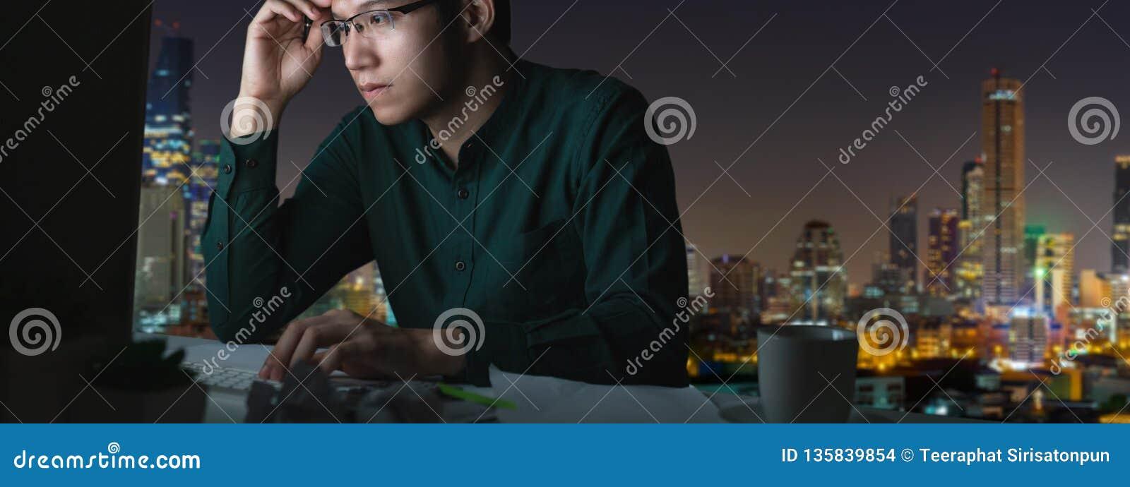 年轻亚裔人横幅坐书桌桌工作晚和坚硬与计算机膝上型计算机在办公室有夜光城市视图