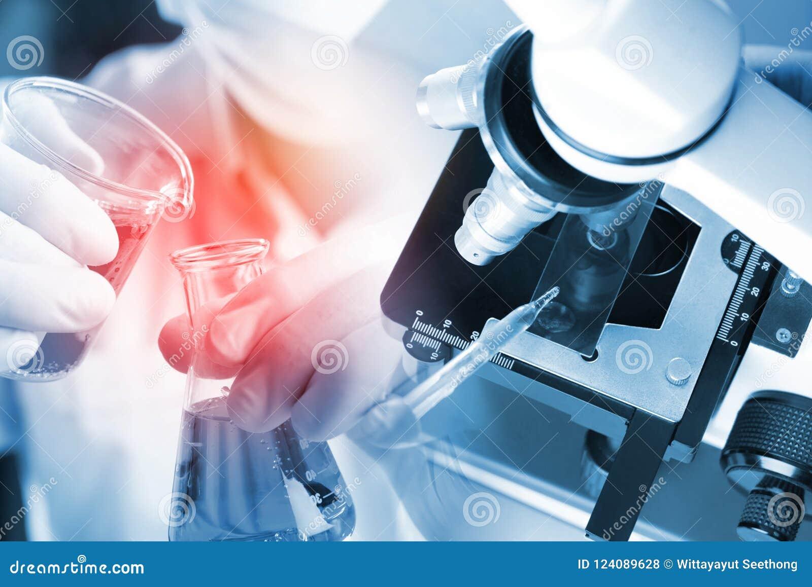 年轻亚裔学生男孩和白色测试的显微镜在有红色液体的科学实验室和吸管