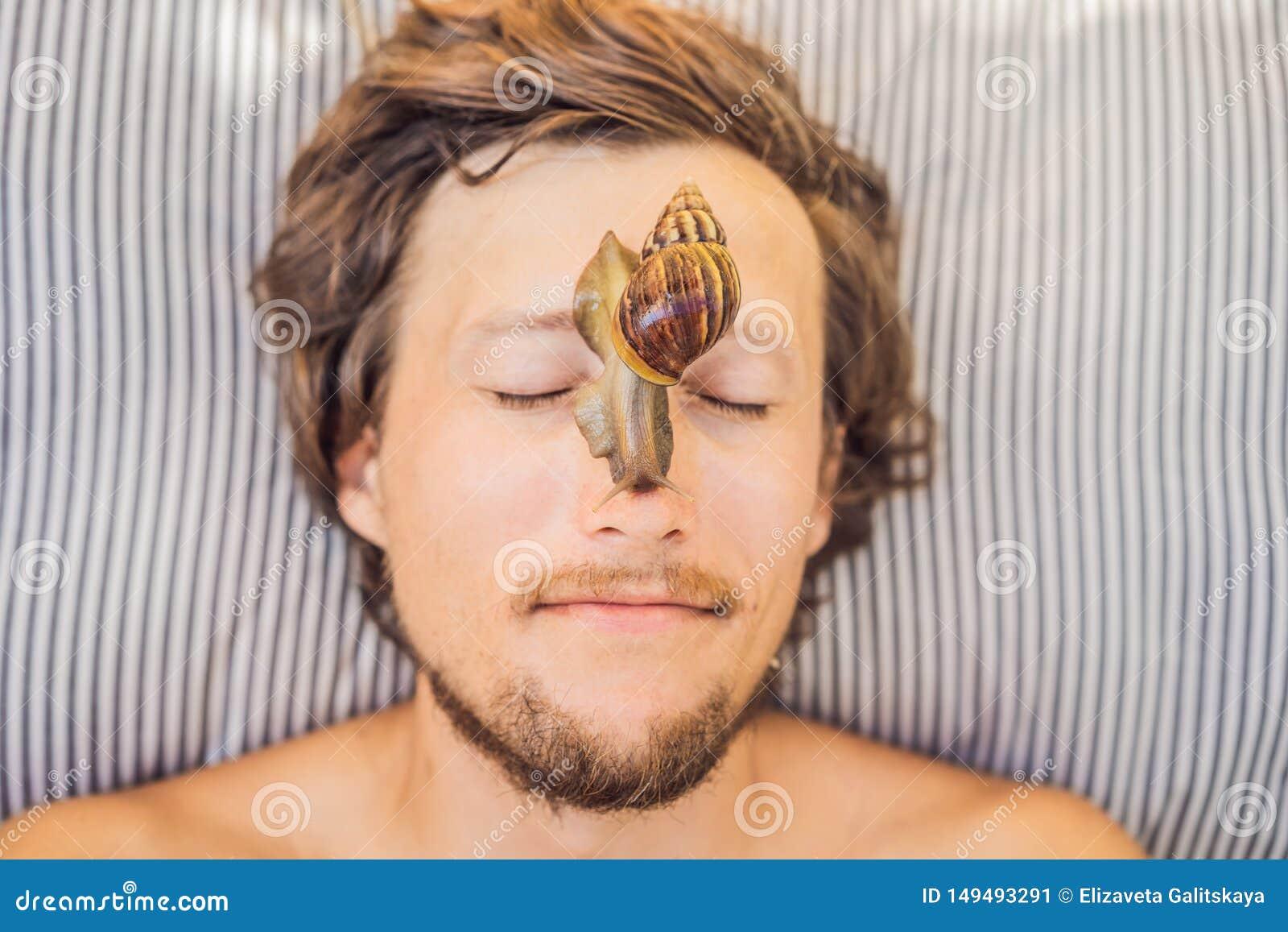 年轻人做与蜗牛黏液的一面膜 爬行在面膜的蜗牛 人的温泉,所有的温泉