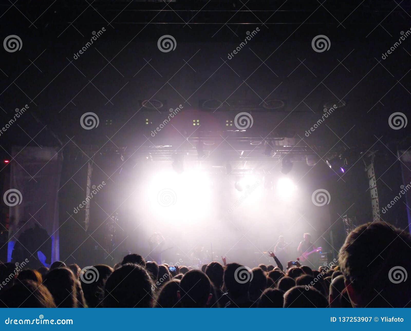 年轻人剪影在一个场面前的在音乐会 摇滚小组 人人群音乐会的